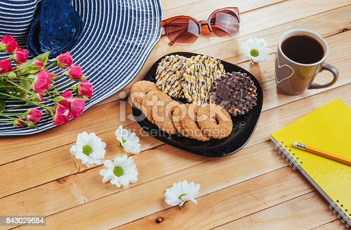 885959540 istock photo Coffee espresso stands on a wooden table with cookies, pad and pencil. 843029684