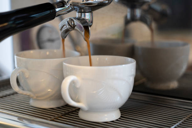 Coffee expresso pouring into 2 white cups stock photo