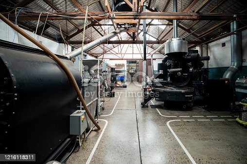 A wide-view shot of a coffee bean roasting and grinding factory, large machinery can be seen around the room.