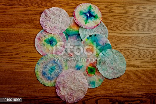 Kid-friendly arts and craft project in which the kids color on coffee filters with washable markers and then spray their designs with water. The coffee filter absorbs the water and the colors run together.