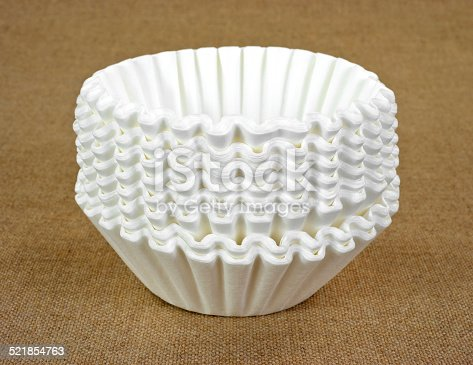 A stack of new white coffee filters on a tan cloth background.