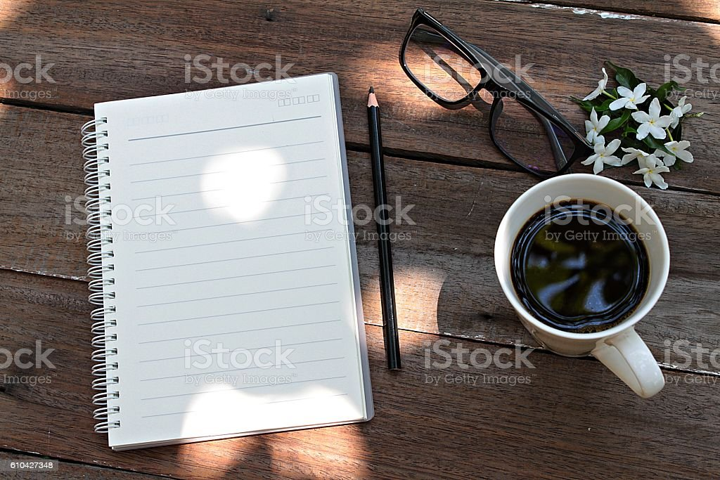 Coffee, glasses, notebook paper, pencil and flowers on wood background stock photo
