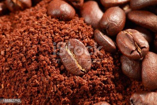 Coffee grains macro with coffee powder below them.