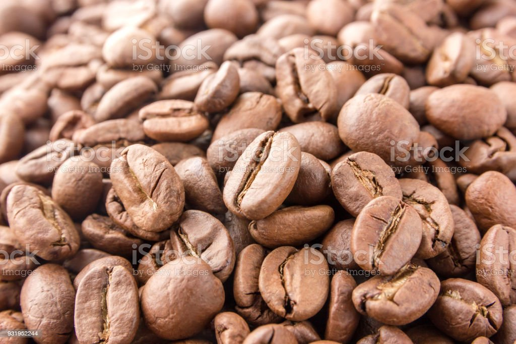 Coffee grains are scattered all over the surface. Roasted coffee beans close-up. stock photo