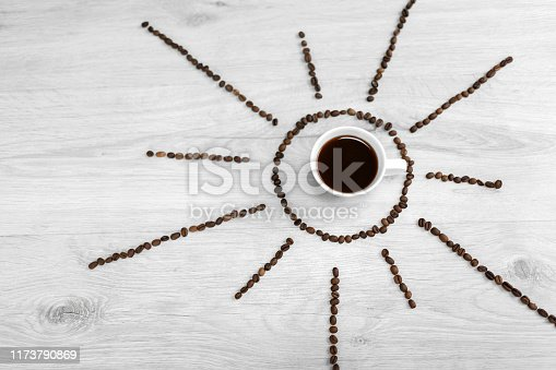 Coffee grains folded in the form of the sun on a wooden background. In the middle is a cup of coffee, meaning it's time to drink coffee after sunrise.