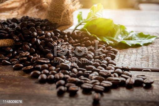 istock coffee grains in bag and leaves. 1148009076