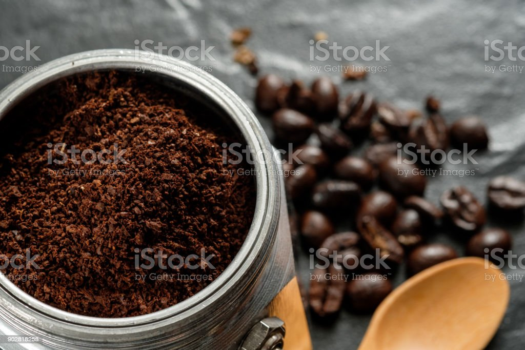 Coffee grounds in moka pot and coffee beans close to wooden spoon on...
