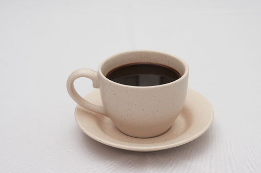 Coffee in a ceramic cup on white table background.