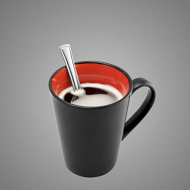 Coffee in a red and black mug with spoon stock photo