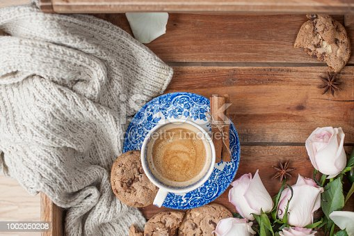 coffee-in-a-vintage-cup-on-a-wooden-background-and-a-bouquet-of-white-picture-id1002050208