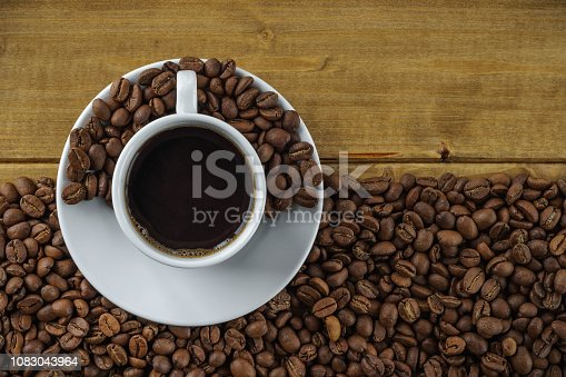 914465180istockphoto coffee in a white cup on a saucer against the background of wooden boards and roasted coffee beans. top view 1083043964