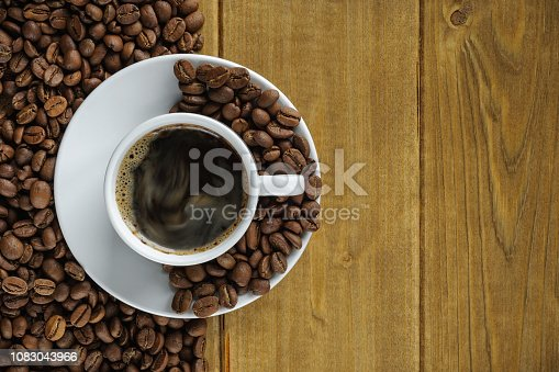 914465180istockphoto coffee in a white cup on a saucer against the background of wooden boards and roasted coffee beans. top view 1083043966