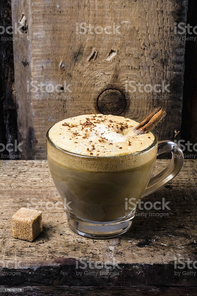 Coffee in glass cup with cream, cinnamon and  sprinkled chocolat royalty-free stock photo