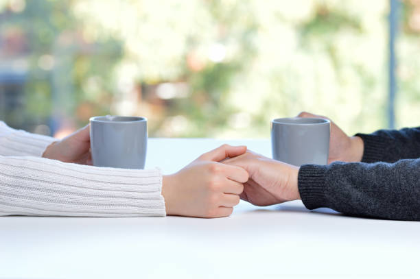 coffee in good company Close up of a couple hands dating and caressing in a bar or home interior human relationship stock pictures, royalty-free photos & images
