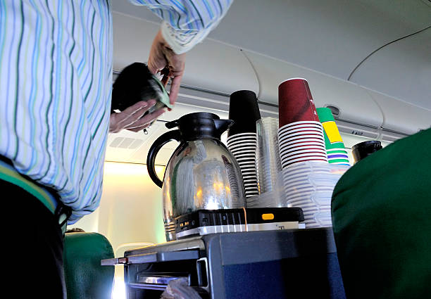 Coffee in the airplane Steward pouring coffee in the cabin of an airplane cabin crew stock pictures, royalty-free photos & images