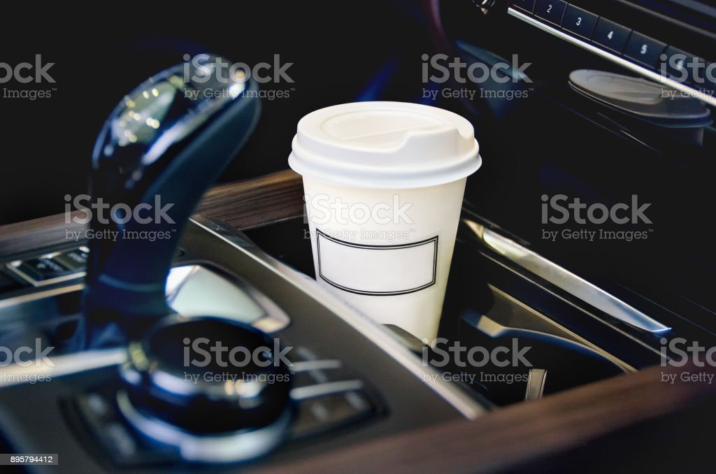 Coffee in the car salon. A single paper coffee cup inside the car cup holder. stock photo