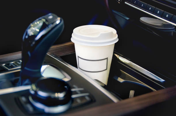 coffee in the car salon. a single paper coffee cup inside the car cup holder. - car interior stock photos and pictures