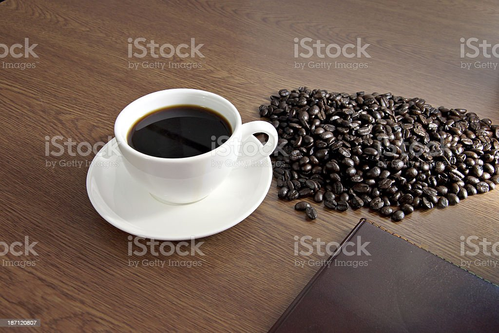 Coffee in white cup and a seed is placed nearby. royalty-free stock photo