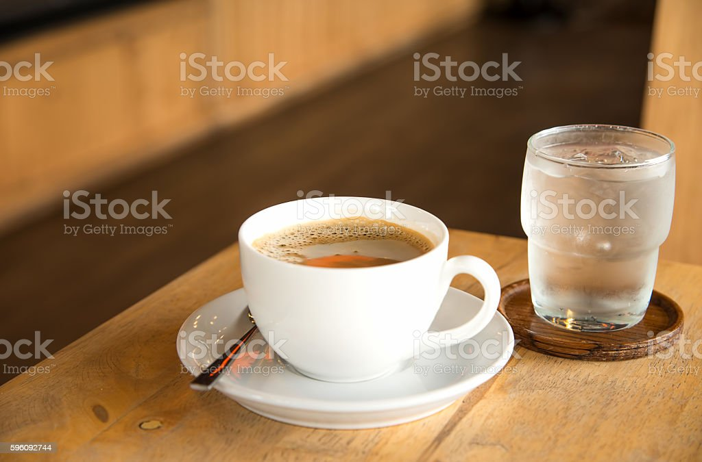Coffee in white cup and glass water on wooden table. royalty-free stock photo