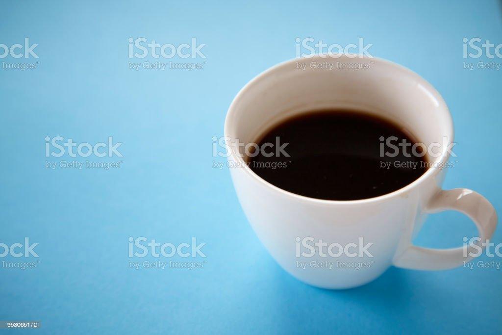 Black coffee in white mug on blue pastel background