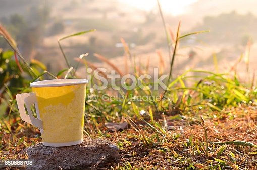 istock Coffee in yellow cup with nature view behind. 680888708