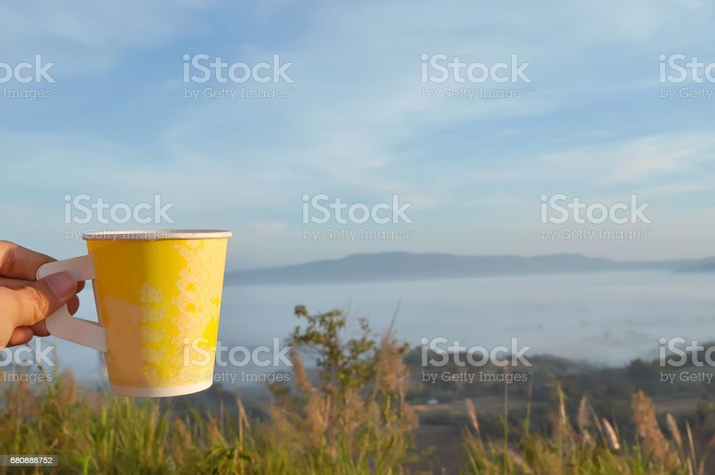 Coffee in yellow cup with nature view behind. royalty-free stock photo