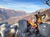 Coffee is always a good idea. Moka on the fire in winter mountains panorama. Lagarina Valley, Italia.