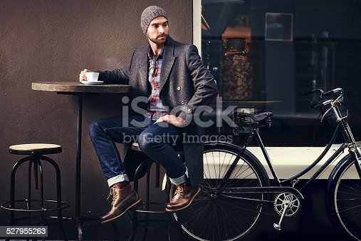 Shot of a handsome young man in winter wear having a beverage at a sidewalk cafe