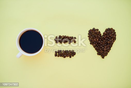 Studio shot of coffee next to an equal sign and heart of coffee beans against a yellow background