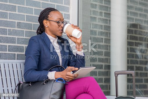 Beautiful young businesswoman drinking coffee out of a paper cup as she is using her digital tablet and sitting with her luggage while she waits for her flight.