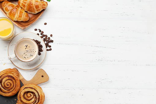 Coffee, croissants, orange juice, cinnamon rolls and berries breakfast. On wooden table. Top view with copy space for your text