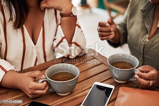 Cropped shot of two women chatting and having coffee at a cafe