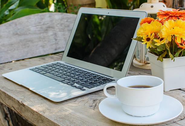 tasse kaffee und laptop auf holz etage mit blume - www kaffee oder tee stock-fotos und bilder