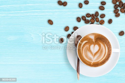 Latte coffee up with scattered roasted coffee beans on pastel blue table background, top view.  Coffee Latte and coffee beans