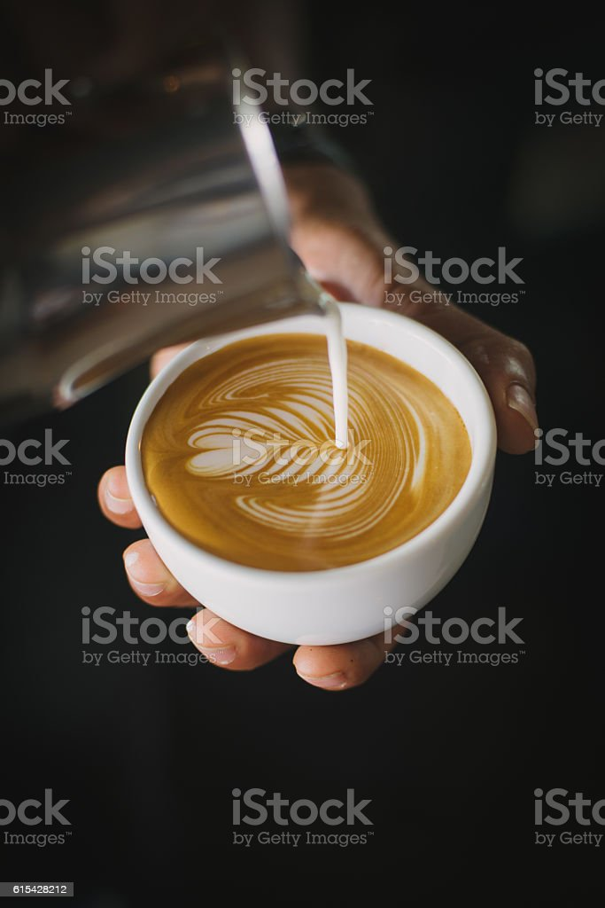 coffee latte art make by barista in coffee shop cafe vintage color...