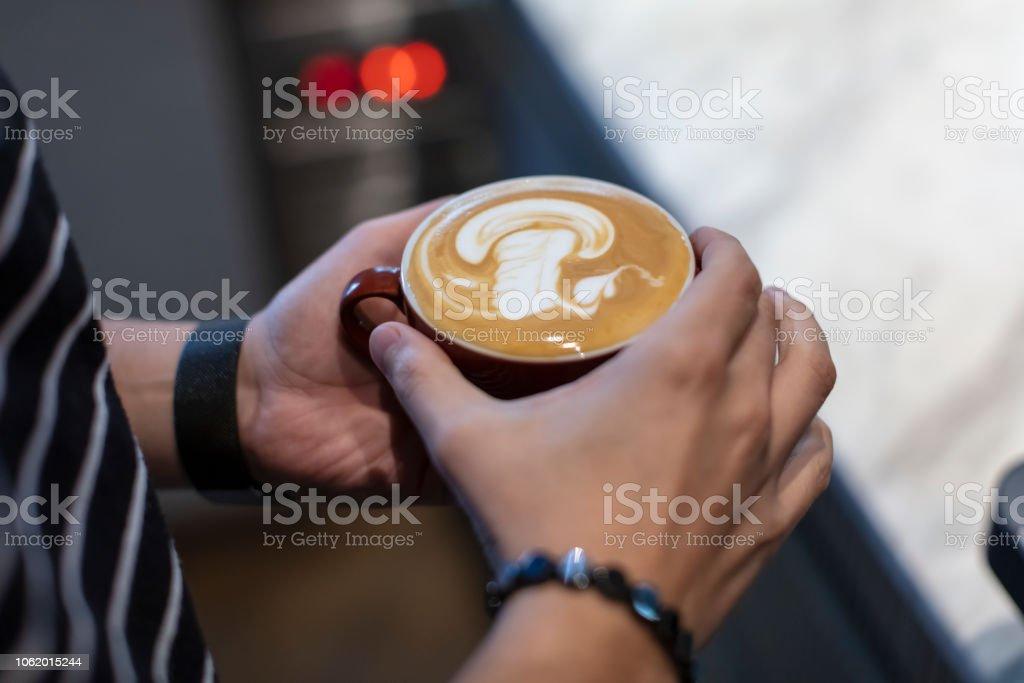 Coffee Latte Art on Man Hand in Coffee Shop