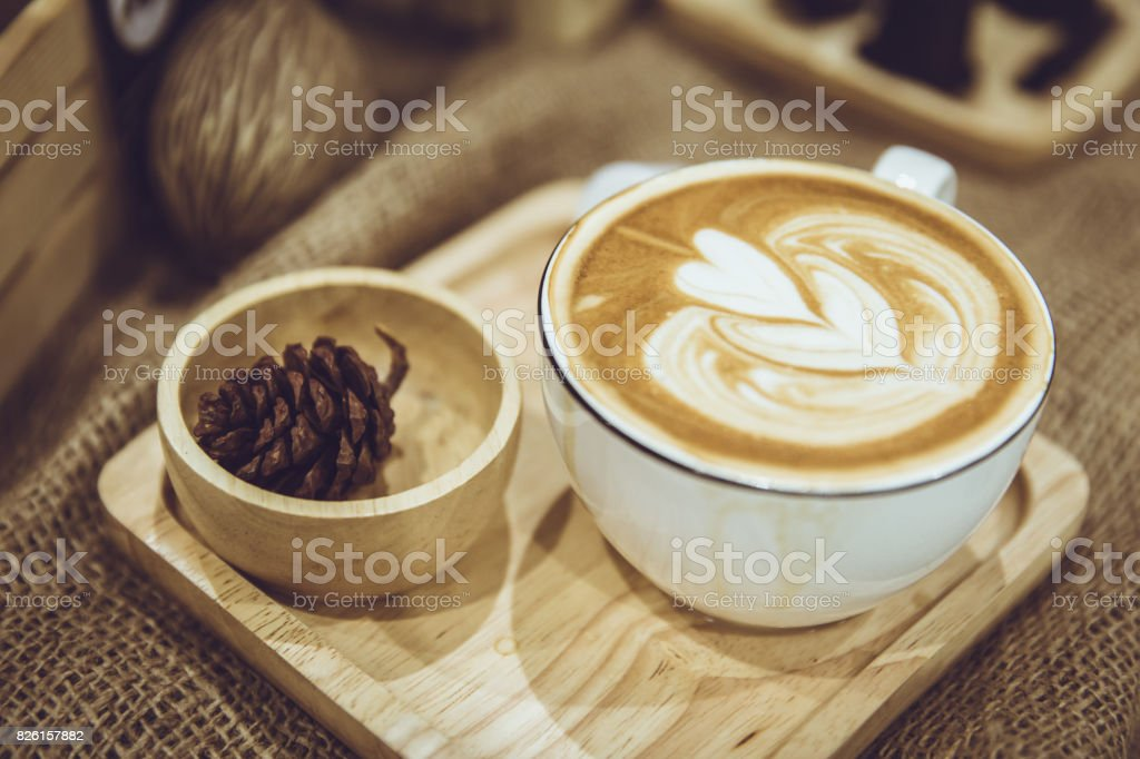 coffee latte art served on wood plate decorated in cafe brown color tone vintage style. stock photo