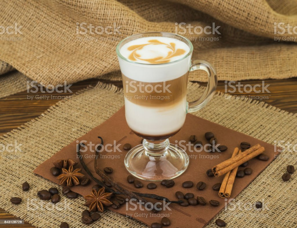 Coffee Latte. Coffee with whipped cream topping in a tall glass on a wooden background with burlap stock photo
