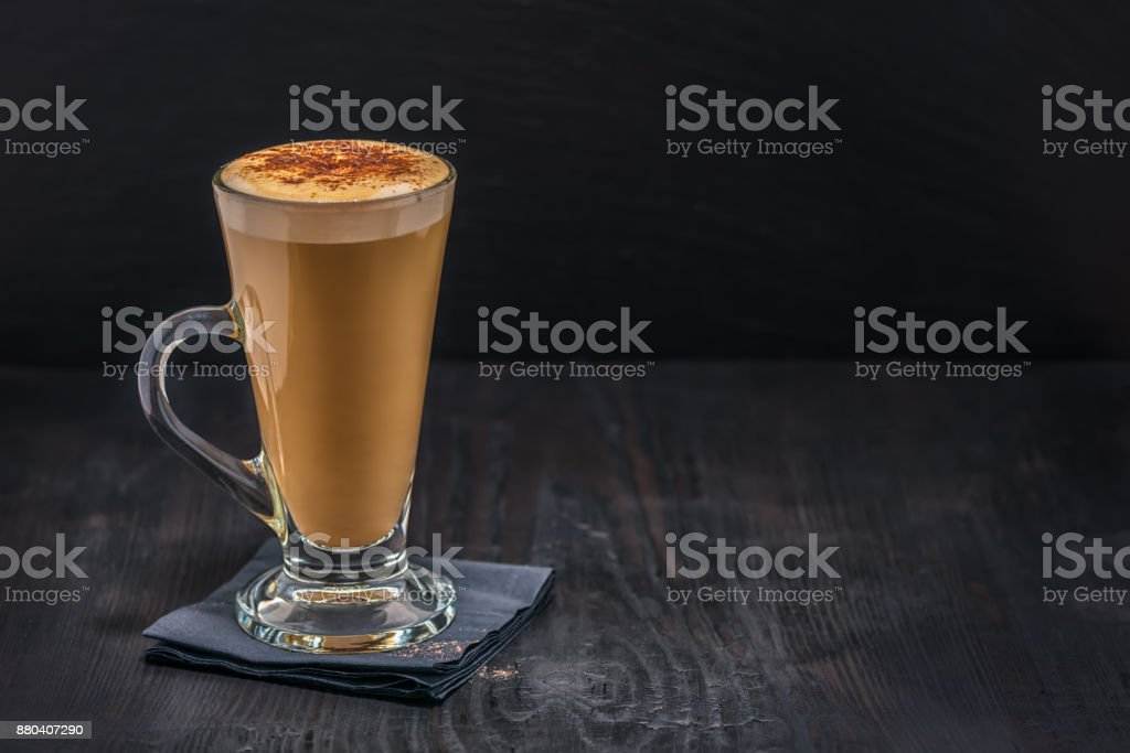 coffee latte in glass with froth of milk on black paper napkin over wooden table stock photo