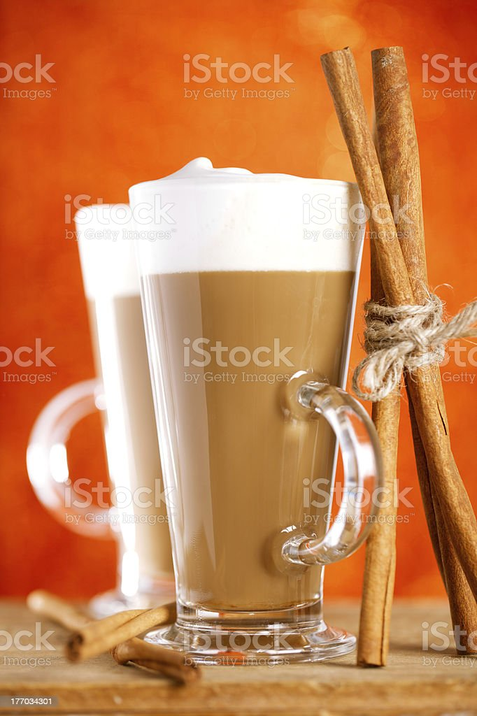 coffee latte with cinnamon sticks, red glitter backdrop, shallow royalty-free stock photo