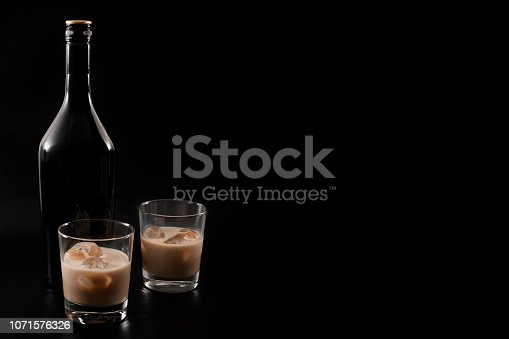 Coffee liqueur and alcoholic beverages based on milk and whiskey concept with Irish cream bottle and glasses with ice isolated on dark black background with copy space
