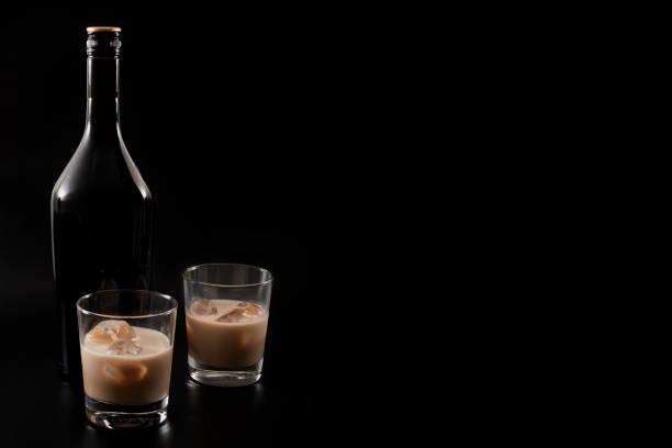 kaffee-likör und alkoholische getränke, basierend auf milch und whiskey-konzept mit irish creme flasche und gläser mit eis auf dunklen exemplar auf schwarzem hintergrund isoliert - schokolikör stock-fotos und bilder