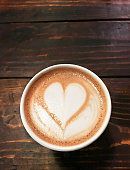 Coffee with a heart shape on a wood background.