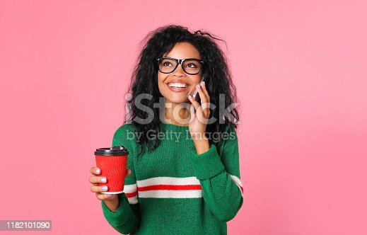 909457386istockphoto Coffee lover. Beautiful African American girl in a green sweatshirt and black glasses is posing with a red coffee cup in her right hand and a smartphone near her left ear. 1182101090