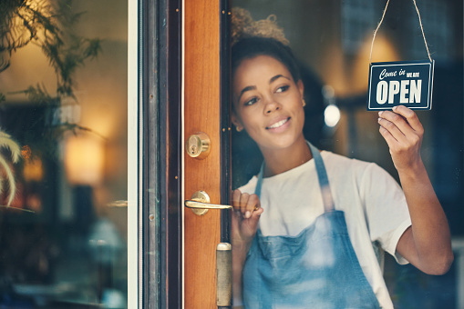 Shot of a young woman hanging an open sign on the window of a cafe