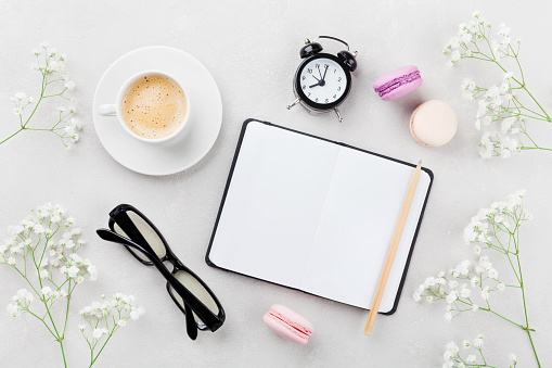 Coffee, macaroons, notebook, eyeglasses, alarm clock and flowers. Lifestyle concept.