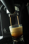 Espresso coffee pouring from coffee machine. Professional coffee brewing
