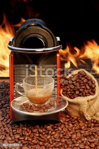 Сoffee machine pours espresso in a glass сup against the bright flame
