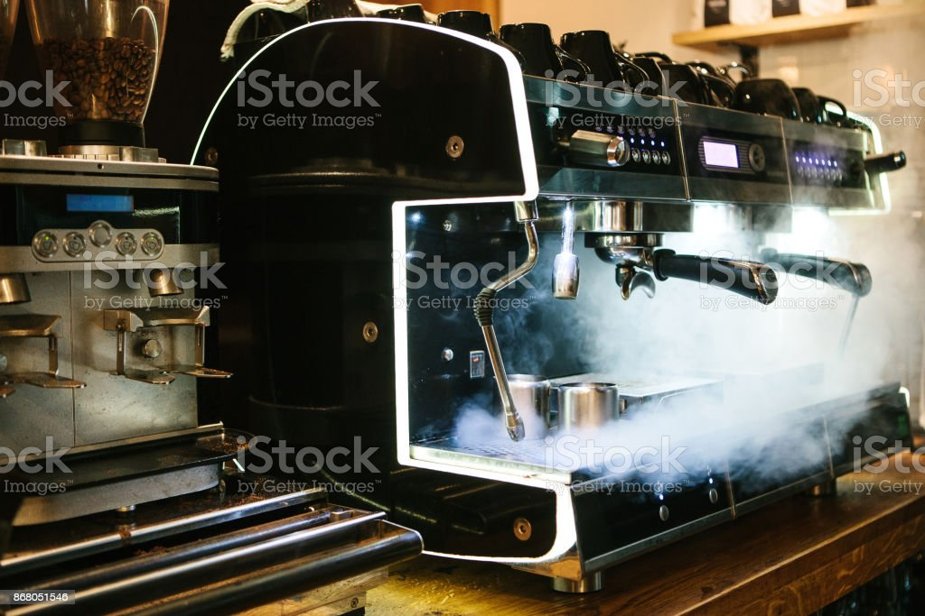 Coffee machine with steam in the process. A cafe stock photo