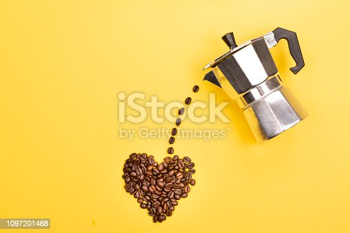Coffee beans pouring from coffee maker into a heart shape on yellow background. Love coffee concept. Flat-lay, top view.